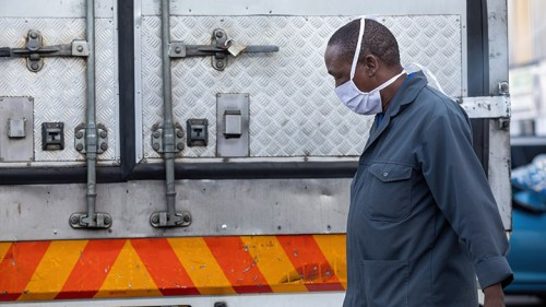 A Worker in Sub-Saharan Africa standing near a truck is seen wearing a mask