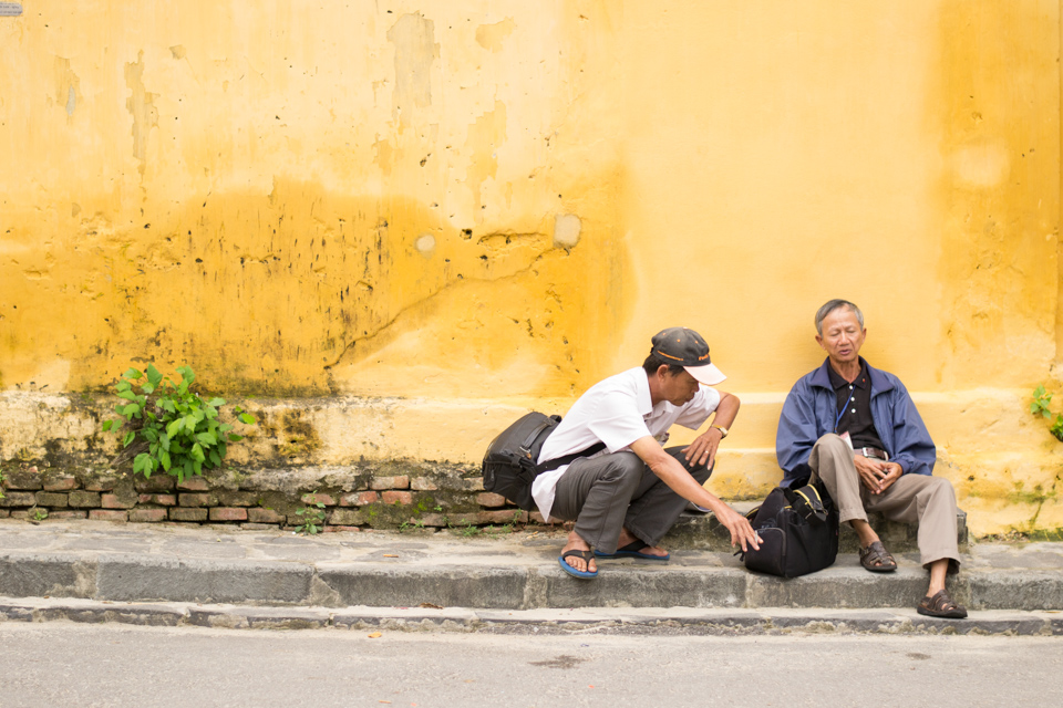 Vietnamese men sitting and talking on the sidewalk