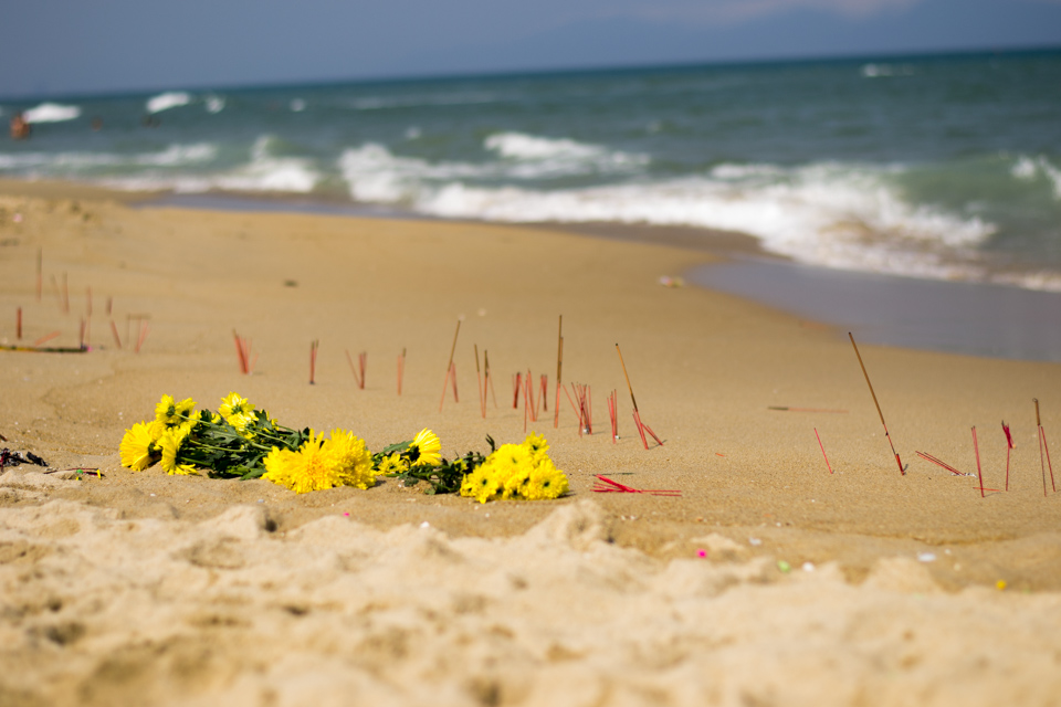 Yellow flowers and burning incense as offerings line the beach