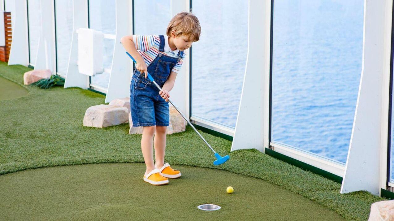 Boy playing mini golf min