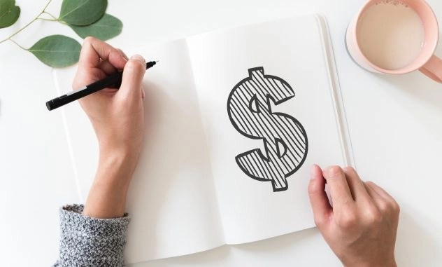 Woman drawing a big dollar sign on paper for very basic info about taxes for freelancers