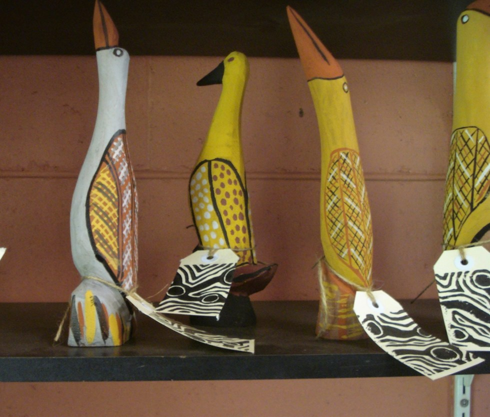Four Aboriginal sculptures of yellow, orange and white birds on a shelf at an art shop on Bathurst Island