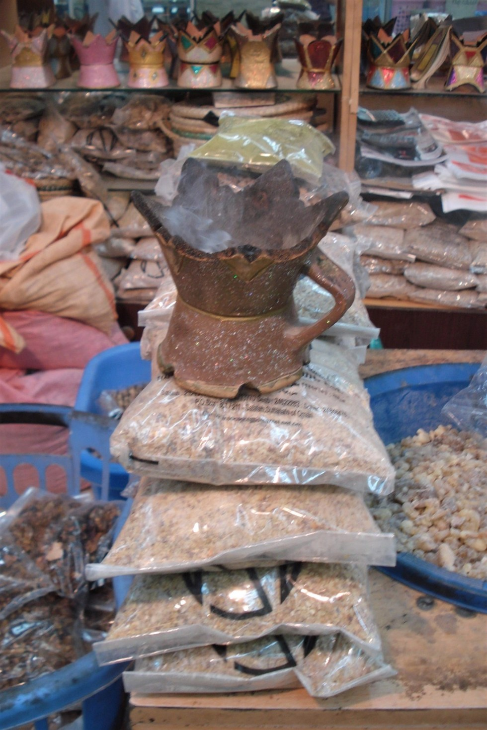 Frankincense burning in a burner atop several plastic bags of frankincense