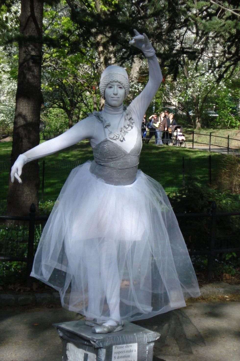 Woman imitating a statue, painted in silver, wearing a silver bodice, white hat and a white tutu with her arms raised gracefully in a ballet pose
