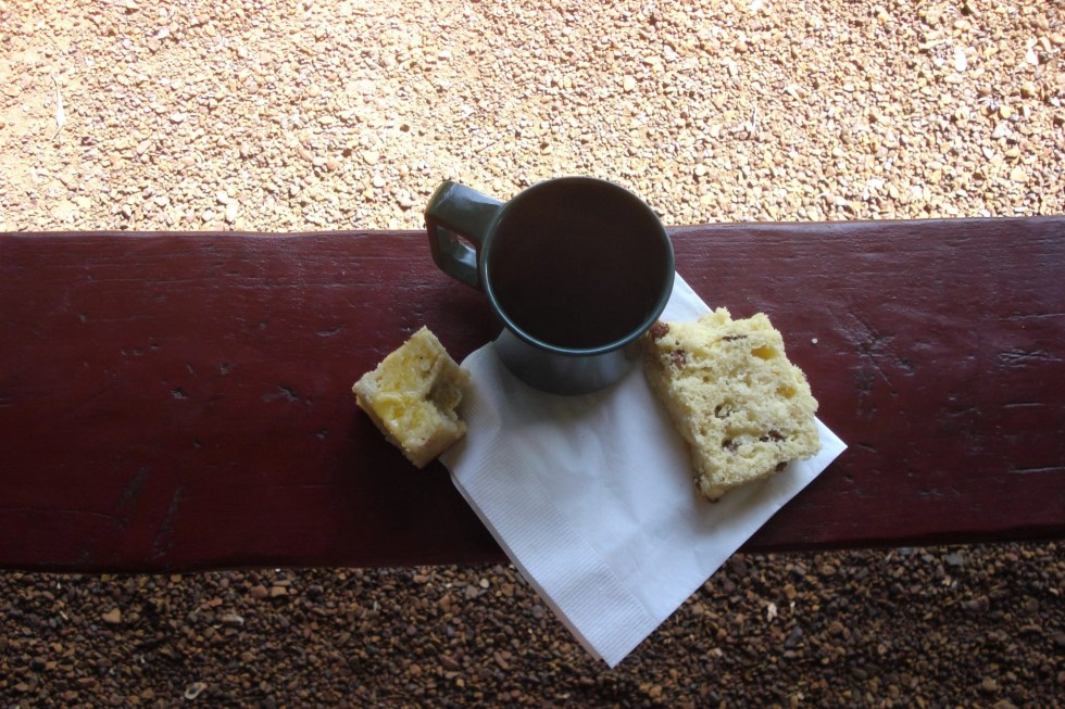 Damper bread and Billy tea on a white paper napkin on top of a wooden rail on the island of Bathurst which I visited on my Tiwi Islands tour