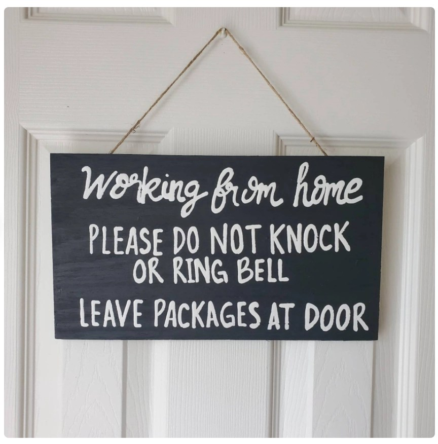 Etsy black sign hanging on white front door with white text saying working from home please do not knock or ring bell leave packages at door