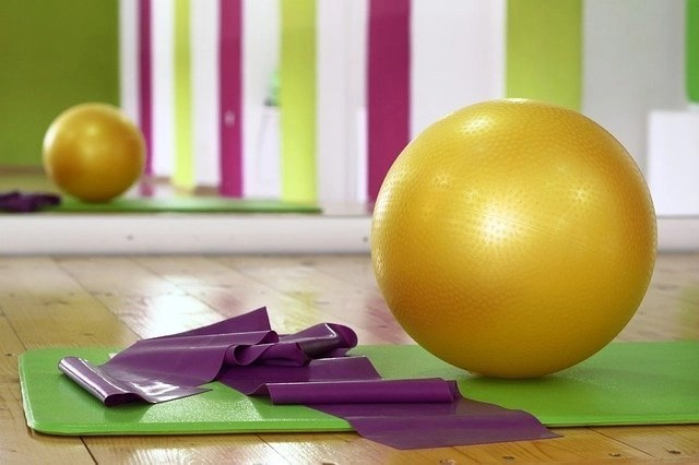 Yellow excercise ball and purple exercise band to help you stay focused when you work at home