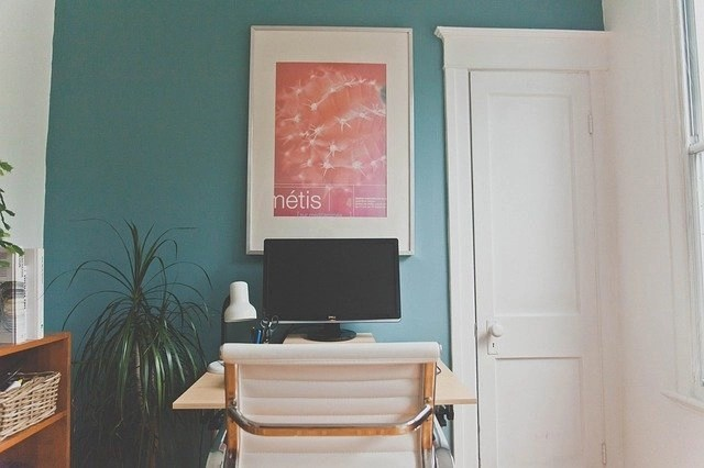 Working At Home On A Desktop Monitor On Desk With A Pink Print Wall Hanging And White Chair Inside A Doorway
