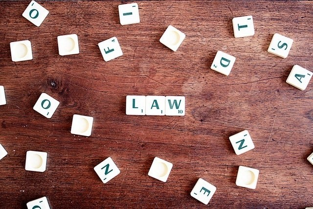 Law Spelled Out In Scrabble Pieces With Other Scrable Pieces Scattered On A Wooden Table