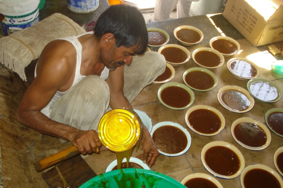 Man squatting on the ground in a factory in Salalah, Oman, pouring hot, freshly made Omani halway into white ceramic bowls to sell.
