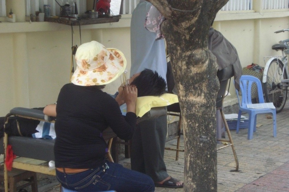 Woman cleaning man's ear on a chair on a sidewalk in Nha Trang, Vietnam