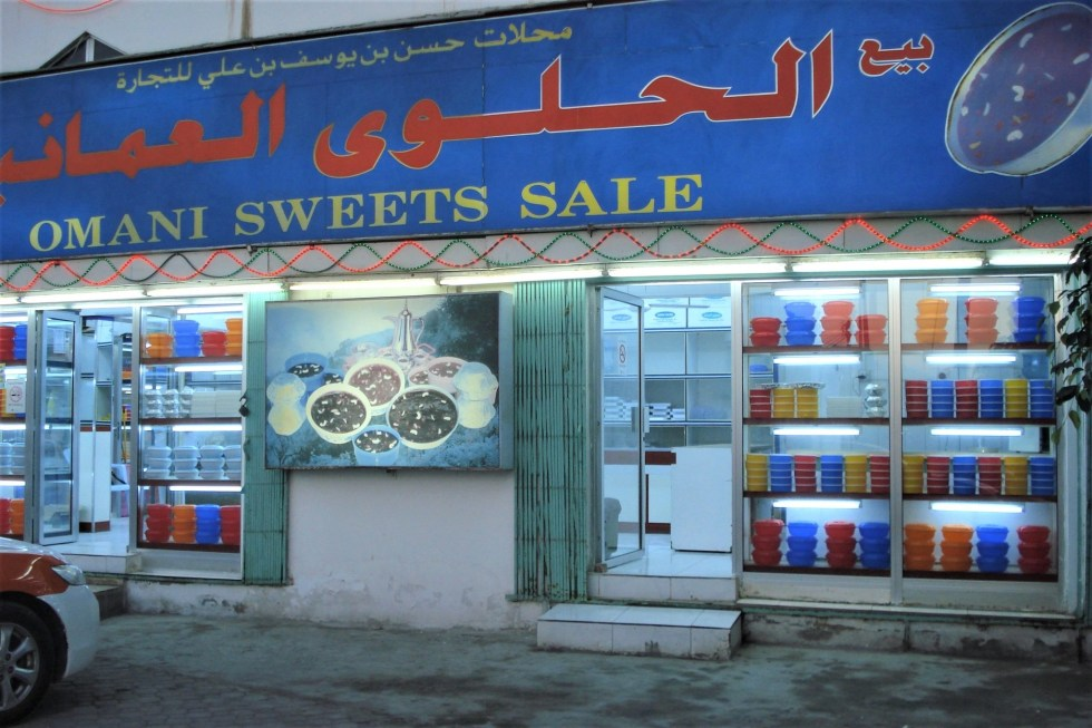 Colorful shop in Salalah, Oman with blue sign in red Arabic lettering and yellow English lettering saying Omani Sweets Sale with colorful round plastic bowls full of Omani halwa in the windows.