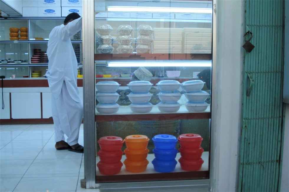 Side view of male Omani shopkeeper standing and looking at glass case full of colorful round plastic bowls of Omani halwa in Salalah, Oman