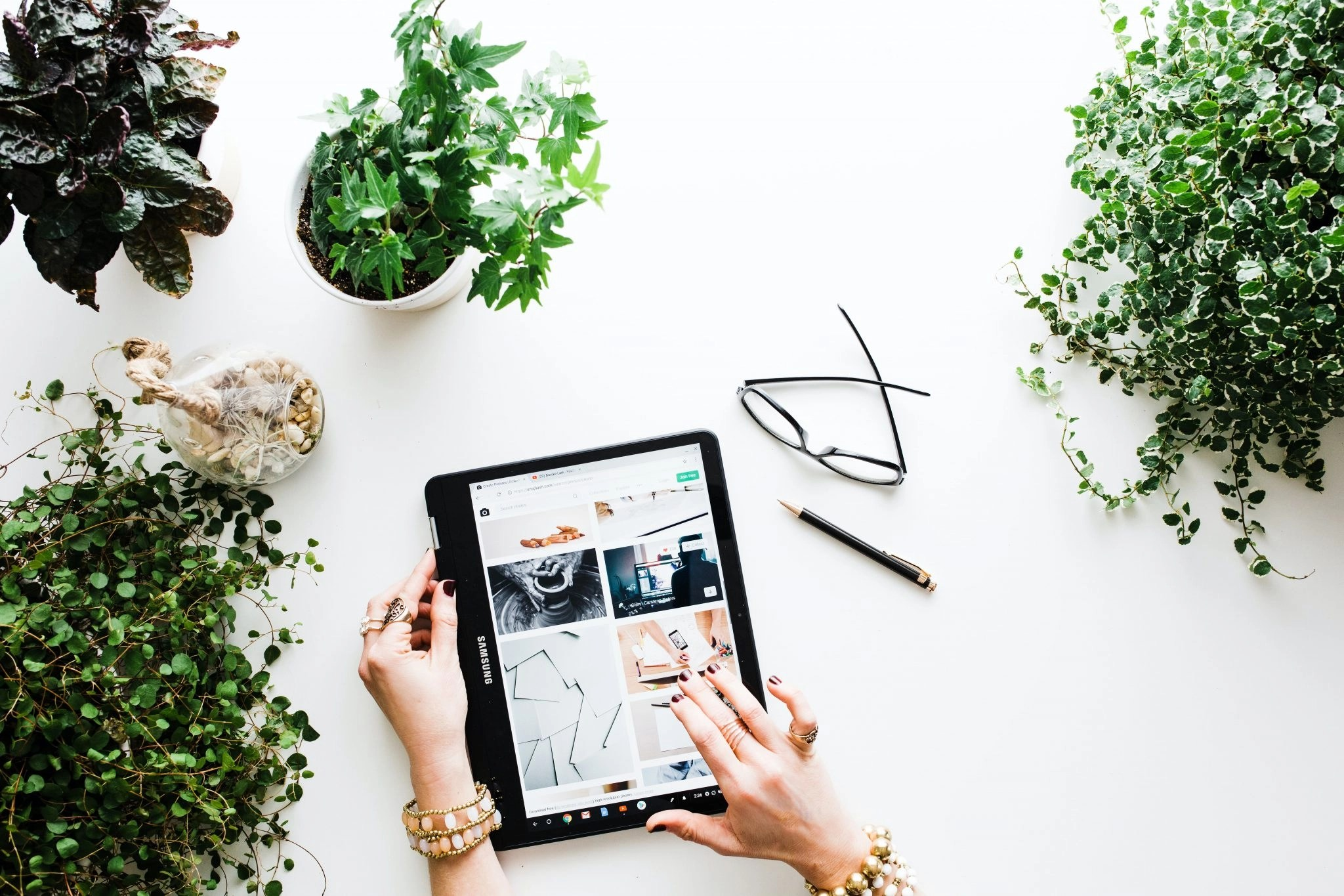 Woman's Hands Selecting Item She Is Selling On Etsy On A Tablet, Surrounded By Plants
