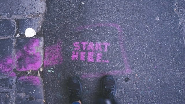 Start here in purple paint on sidewalk with black boots standing over it for the benefits of freelancing