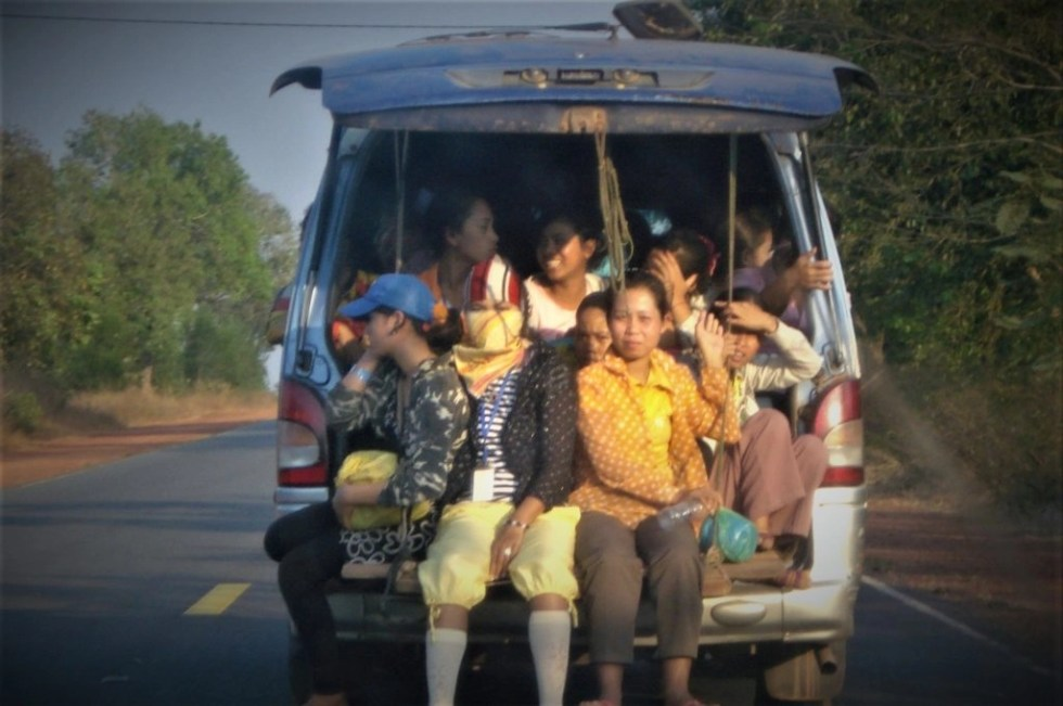 Cambodan women hanging out of the back of a truck on the road to Kampot, Cambodia