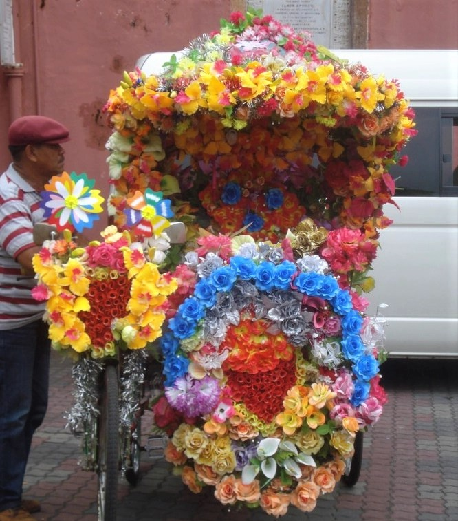 Malaysian man standing beside a trishaw completely covered in colorful flowers in Melaka