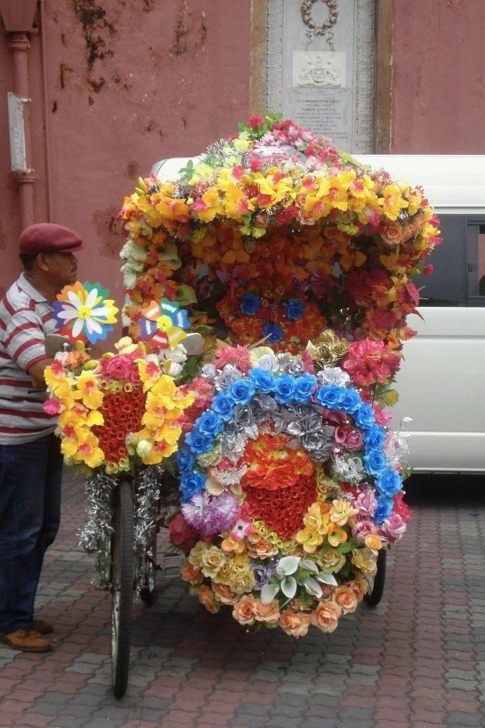 Riding a tuk-tuk covered in colorful flowers in Melacca, Malaysia is one of the advantages of travelling on a budget