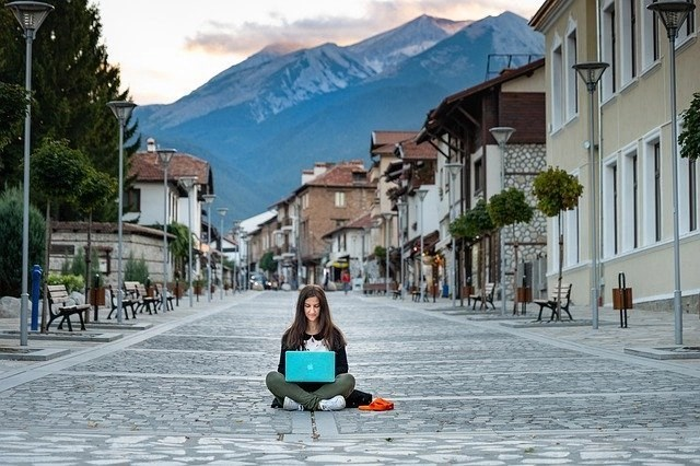 Woman sitting on empty street lined with buildings with snowcapped mountains in the back ground, working on a laptop