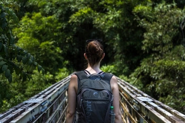 Woman who makes money while traveling, walking across a bridge with her backpack
