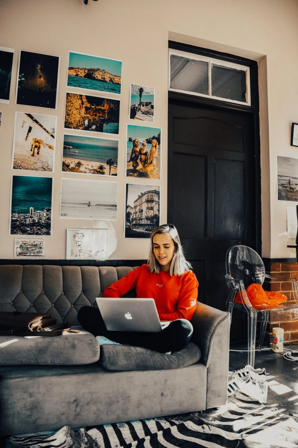Young woman with straight gray hair in red sweater sitting on grey sofa in room with tall black door with glass on top and several large unframed photos on the wall behind her looking for side hustle ideas