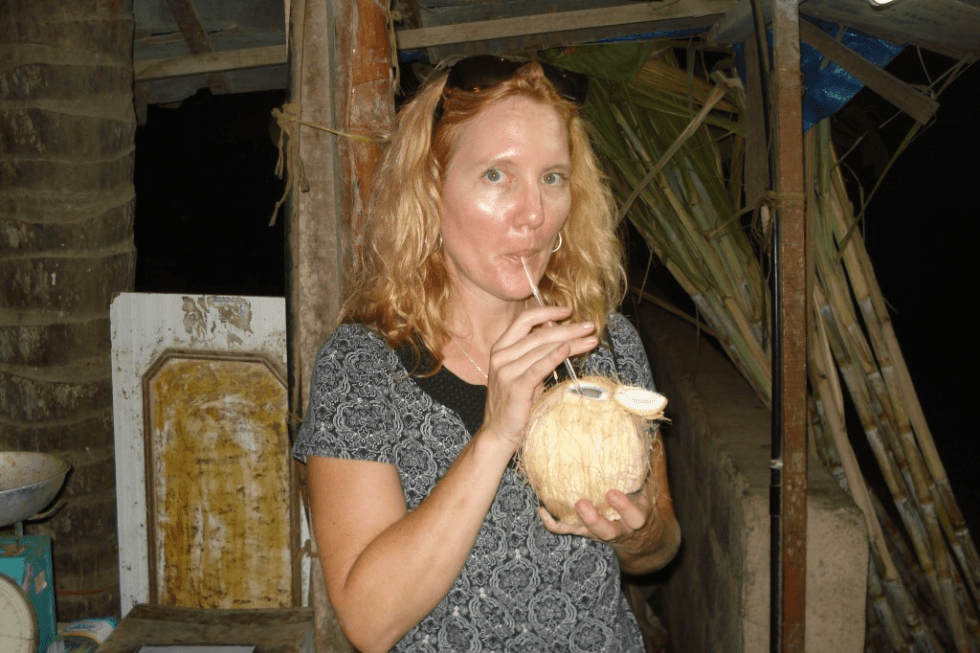 Me drinking coconut milk with a straw in a little ramshackle hut on my Salalah, Oman tour