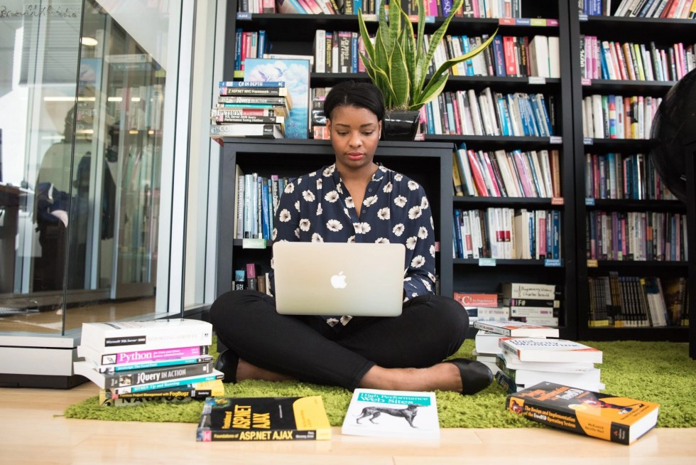 Black woman in black pants and black and white blouse sitting cross legged on floor holding Mac book surrounded by books on floor and on shelves looking for side hustle ideas