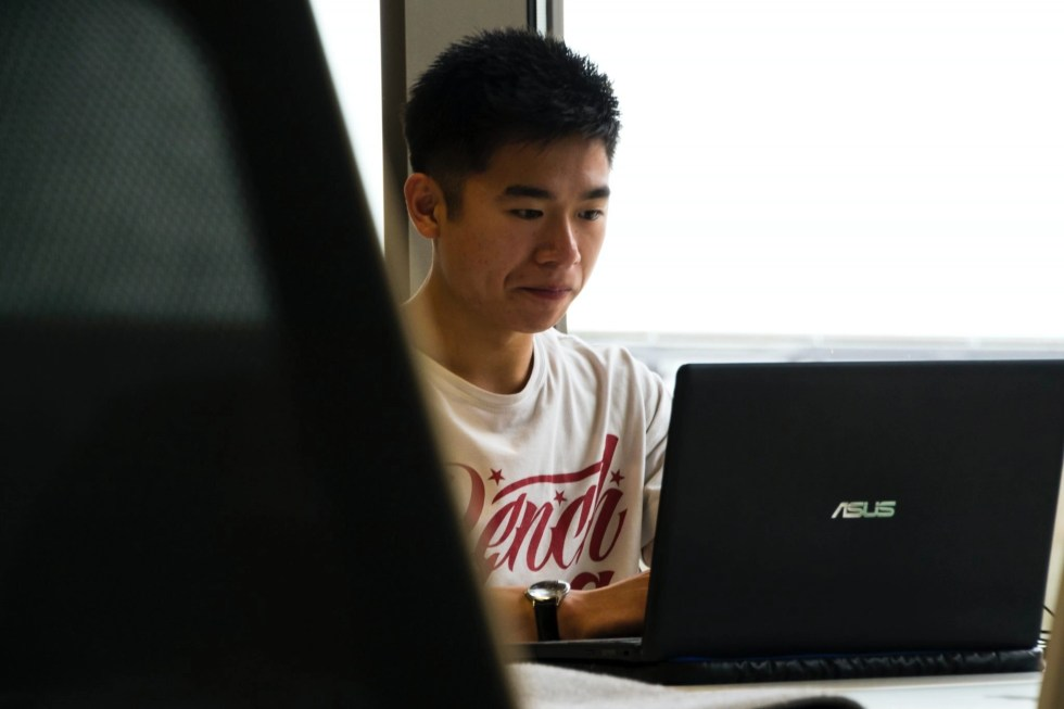Young man wearing T-shirt sitting at an Asus computer working on a virtual assistant job from home