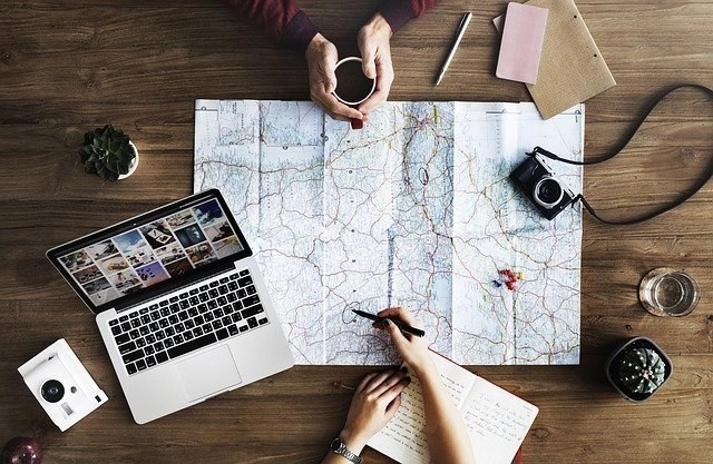 Map, Cameras And Laptop To Freelance Online While Traveling