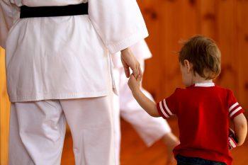 Woman karate kimono holds her child's hand