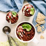 picture of chili in bowls on a light-colored table with blue cloths and measuring spoons around them. The chili is drizzled with cashew sour cream and slices of avocado on top.