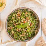 Tabbouleh salad served in a dish with pita and hummus