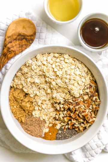 Large white bowl with homemade granola ingredients, a small bowl with maple syrup on the side