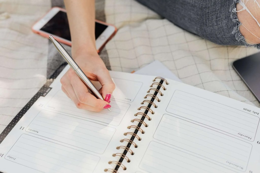 crop woman taking notes in diary while sitting in park