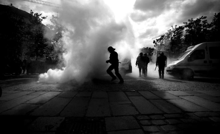 Un CRS évacue un fumigène lancé a ses pieds