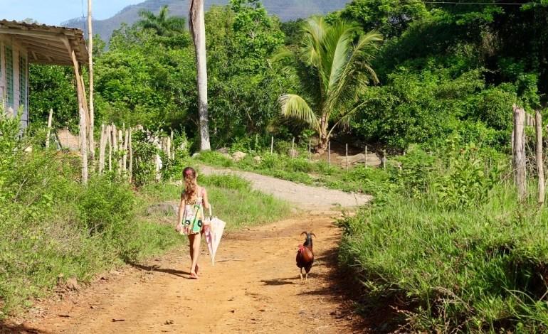 Dans ce hameau, les animaux côtoient au quotidien les habitants. Hasard de l'instant, je prends cette photo lorsqu'un coq et une jeune fille parapluie au bras se croisent dans l'indifférence. © Lucie Martin/Worldzine