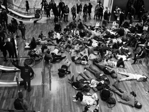 Une partie des manifestants improvise un sitting en plein milieu du centre commercial.