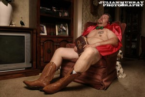 Photo of Will C sitting in a recliner wearing a red cape, green bow tie, brown cowboy boots and nothing else while holding a bible in his lap, staring off camera