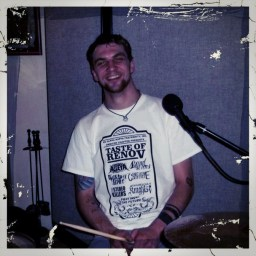 Craig Schrader - drummer for Fighting the Future smiling politely behind a drumset