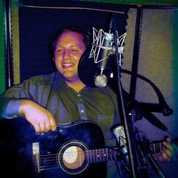 Kyle Dazey smiling with guitar