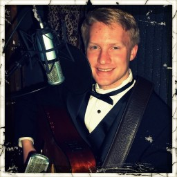 Mason Frey, Reno guitarist, musician and singer, wearing a tuxedo and smiling while holding a guitar