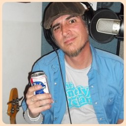 Nick Ramirez, bass player for the Liver Scars, a Reno NV punk rock band, squinting like Popeye and holding a beer