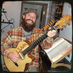 Liam Kyle Kahill, smiling broadly and playing his guitar