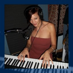 Georgia Maestro playing the keyboard with a sultry smile on her face