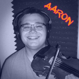 Aaron Long smiling broadly, holding his violin