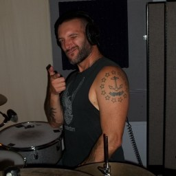 Mike Thompson, drummer for Sit Kitty Sit, winking and 'shooting' at the camera with a 'finger gun'