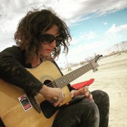 Mallor mishler playing guitar on the playa at Burning Man