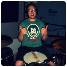 Mike Messerli of Man the Tanks wearing a The Joker t-shirt and giving 2 thumbs up whilst smiling broadly