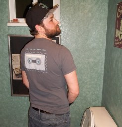 Kyle pretending to pee in a toilet with his back turned to you, but looking over his shoulder.