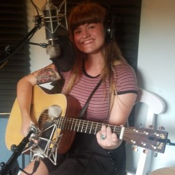 Reno, Nevada singer-songwriter Gina Rose poses with her guitar while recording the Worst Little Podcast.
